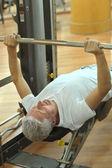 Elderly man playing sports in a gym — Стоковое фото