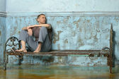 Man on the metal rusty bed in prison — Stock Photo