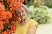 Older woman with yellow flowers — Stock Photo