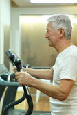 Elderly man playing sports in a gym — Stock Photo