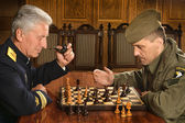 Military mature general playing chess with soldier — Stock Photo