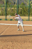 Active senior man playing tennis — ストック写真