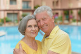 Senior couple standing by pool — Stock Photo