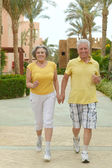 Senior couple run at tropic hotel resort — 图库照片