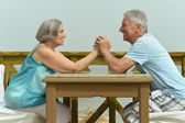 Senior couple sitting at table at beach — Stock Photo