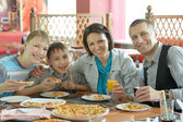 Usmívající se rodina jíst pizzu — Stock fotografie