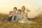 Mom with sons on wheat field — Stock Photo