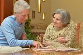 Elder couple sitting at a table at home — Stock Photo
