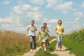 Family running on a dirt road — Stock Photo