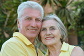 Elderly couple on palm leaves background — Stock Photo