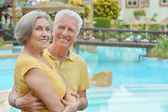 Senior couple by pool at the resort — Stock Photo