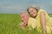 Old couple lying on the field — Stock Photo