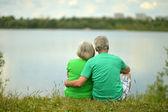 Senior couple near the river — Stock Photo