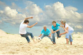Family playing football on a beach — Stock fotografie