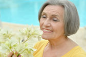 Retired woman posing with flowers — Foto Stock
