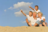 Boys with grandparents sitting on sand — Foto de Stock