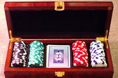 Poker chips and playing cards in wooden suitcase — Stock Photo