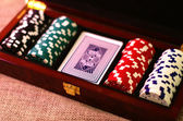 Poker chips and playing cards in suitcase — Stock Photo