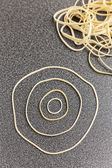 Rubber bands making a design on desktop — Stock Photo