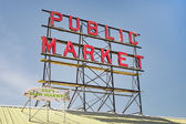Neon public market sign against sky — Stock Photo