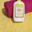 Suntan lotion on beach towel — Stock Photo