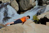 Practicing Yoga at Waterfall — Stockfoto