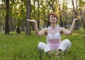 The woman meditates in park — Stock Photo