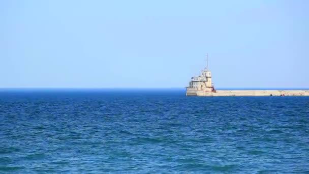Movimiento de las olas del mar contra un muelle con edificio — Vídeo de stock