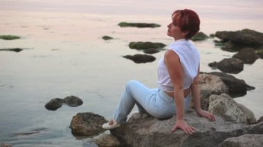 Harmonous woman sits on seashore in the evening — Stock Video