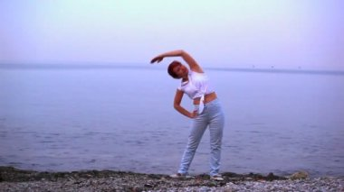 The harmonous woman does exercises on the seashore — Stock Video