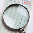 Guest Check and magnifying glass — Stock Photo