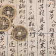 Antique chinese book page and coin — Stockfoto