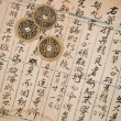 Antique chinese book page and coin — Stock fotografie