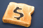 Bread slice with dollar sign — Stock Photo
