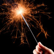 Child's hand, holding a burning sparkler. — Stock Photo #15322705
