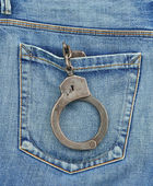 Back pocket of jeans with handcuffs — Stock Photo
