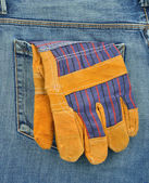 Back pocket of jeans with protective gloves — Stock Photo