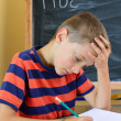Stock Photo: Young boy tries to do his homework