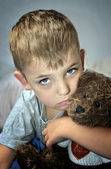 Small sad boy with eye bruise and teddy bear — Stock Photo