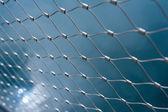 Metallic net with blue background — Stock Photo