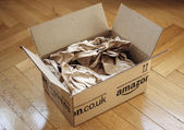 Opened parcel from Amazon on home parquet floor — Stock Photo