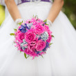 Bride holding wedding flowers — Stock Photo #14241021
