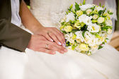 Wedding rings and flower bouquet — Stock Photo