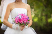 Bride holding pink bouquet — Stock Photo