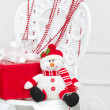 Smiling toy snowman with beads and gift box — Stock Photo