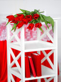 Red flowers on a white stand — Stock Photo