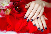 Dark fingernails and beautiful red flowers — Stock Photo