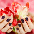 Cupped hands with dark manicure holding red flowers — Stock Photo