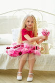 Little beautiful girl in pink dress with flowers in her bedroom — Stock Photo