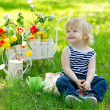 Cute boy in the garden with flowers — Stock Photo